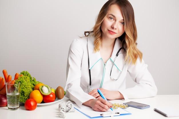 Schöne junge ernährungsberaterin mit frischem gemüse und obst
