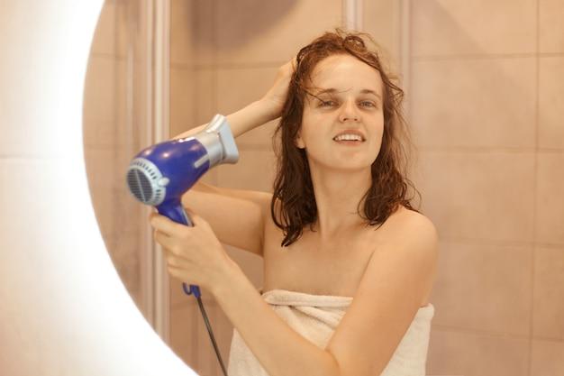 Schöne junge erwachsene dunkelhaarige frau im badetuch, die einen fön benutzt und beim blick in den spiegel im badezimmer lächelt und zufriedenen gesichtsausdruck hat.