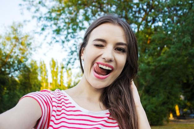 Schöne junge erwachsene frau, die foto von, selfie macht