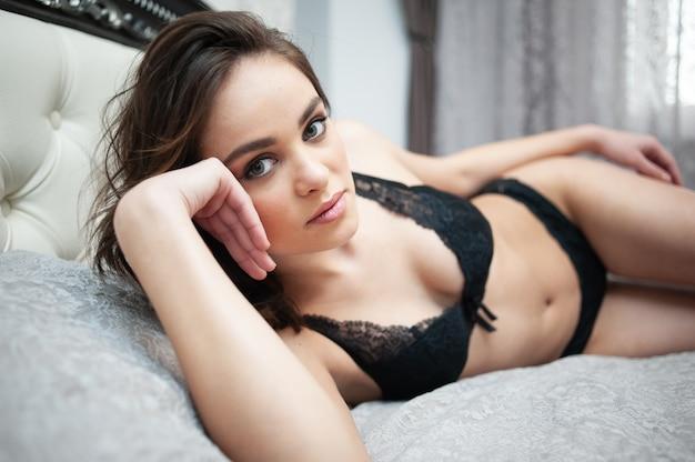 Schöne junge erwachsene sexy frau, die in dessous liegt.