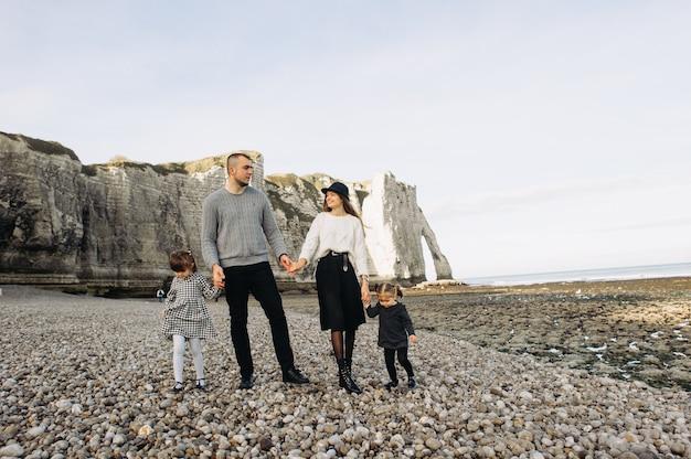 Schöne junge familie am sandigen ufer des ozeans entspannen und spaß haben