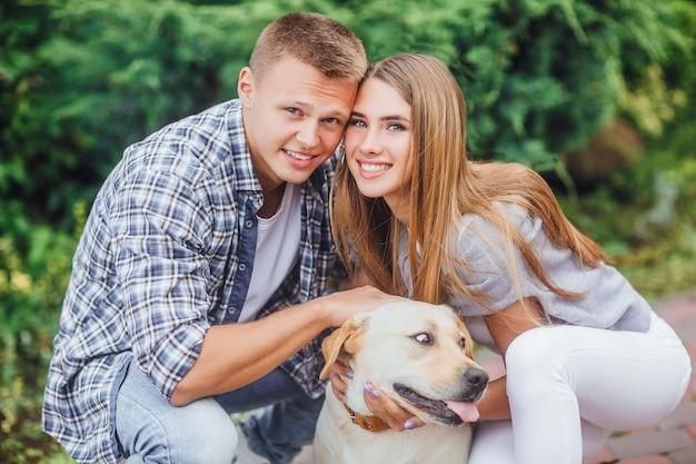 Schöne junge familie, die mit dem hund spielt und in die front lächelt