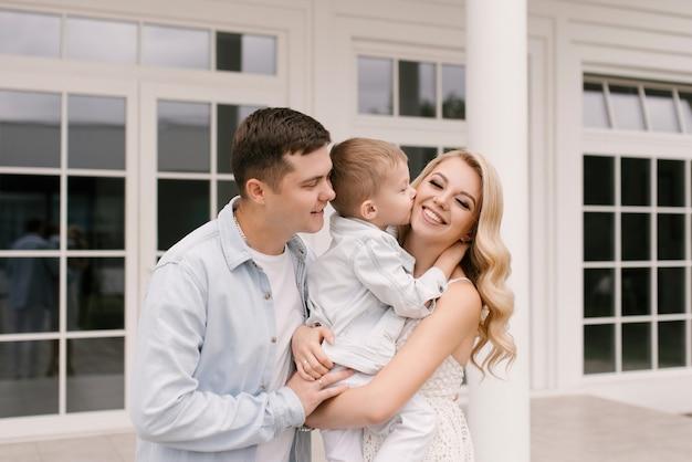 Schöne junge familie mann frau und sohn in intelligenten kleidern auf dem hintergrund eines luxuriösen weißen hauses