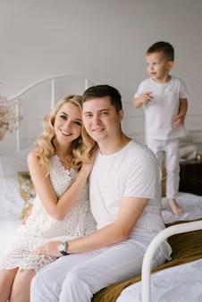 Schöne junge familie mann frau und sohn in weißen kleidern spielen auf dem bett zu hause