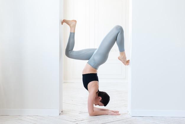 Schöne junge fitness-bloggerin, die einen schwierigen handstand in einem weißen innenhintergrund macht