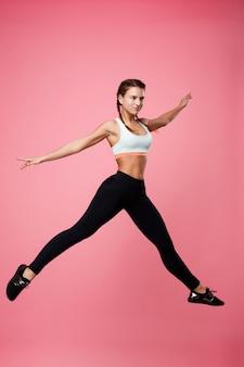 Schöne junge fitnessfrau in buntem top und schwarzen leggings