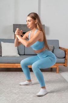 Schöne junge fitte frau in blauer sportbekleidung, die zu hause im gemütlichen interieur kniebeugen macht