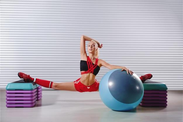 Schöne junge flexible fitnessfrau, die spaltungen während ihres w tut