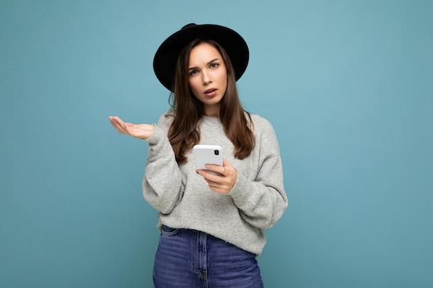 Schöne junge fragende unzufriedene brünette frau mit schwarzem hut und grauem pullover, die smartphone mit blick auf die kamera auf hintergrund isoliert hält. platz kopieren