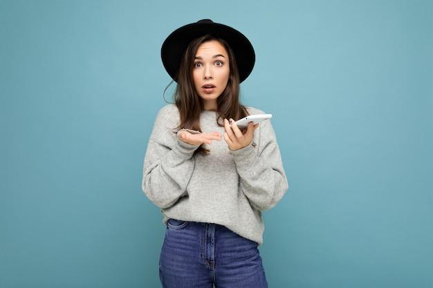 Schöne junge fragende unzufriedene brünette frau mit schwarzem hut und grauem pullover mit smartphone, die die kamera einzeln auf dem hintergrund betrachtet.