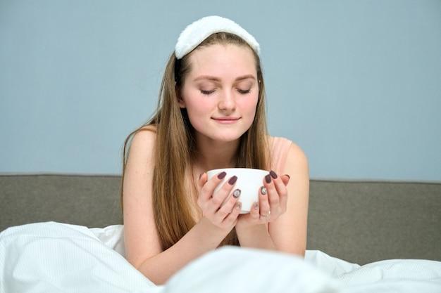 Schöne junge frau 20 jahre alte blondine im bett mit tasse tee, morgen, weißes bett, graue hintergrundwand