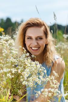 Schöne junge frau auf dem gänseblümchenblumenfeld