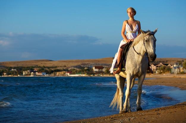 Schöne junge frau auf einem pferd in der nähe des meeres