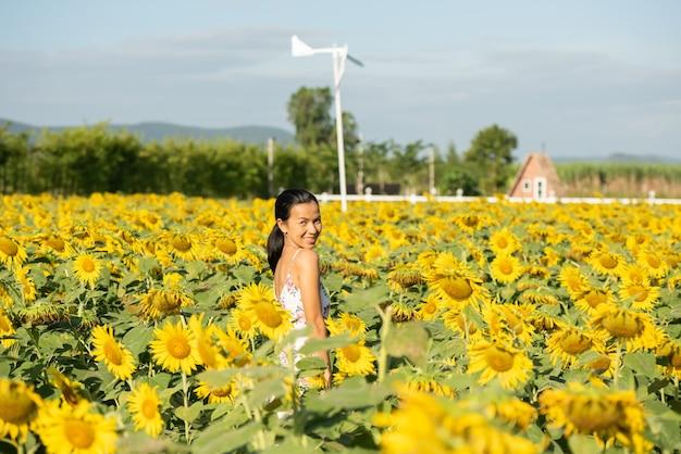 Schöne junge frau auf einem sonnenblumenfeld in einem weißen kleid. reisen sie am wochenende konzept. porträt der authentischen frau im strohhut. draußen auf dem sonnenblumenfeld.