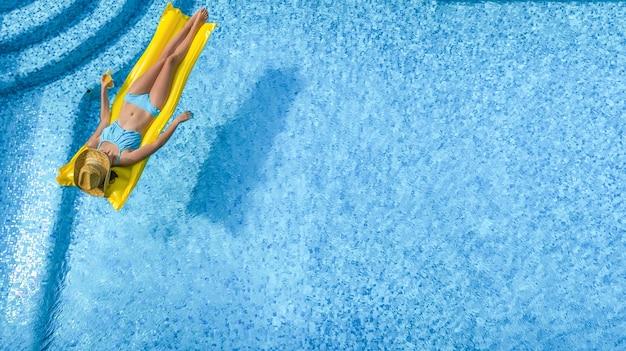 Schöne junge frau auf einer aufblasbaren matratze