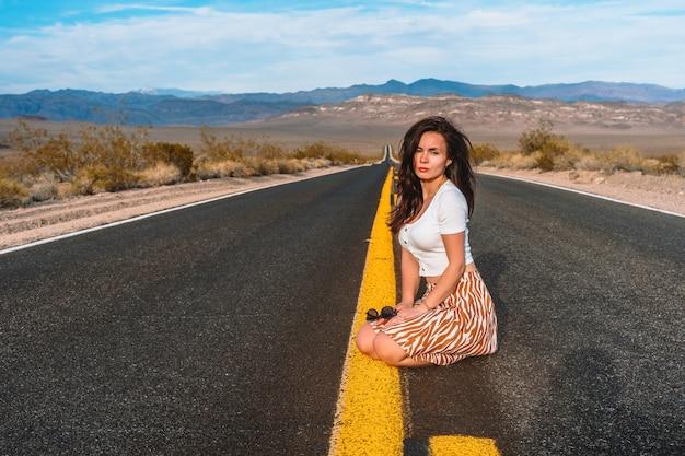 Schöne junge frau auf einer gelben gasse mitten im death valley usa