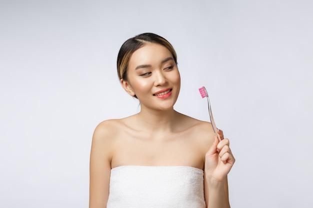 Schöne junge frau auf weißem getrenntem hintergrund hält eine zahnbürste, asiatisch