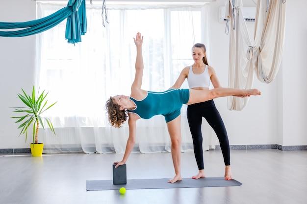 Schöne junge frau beim yoga mit trainer im studio