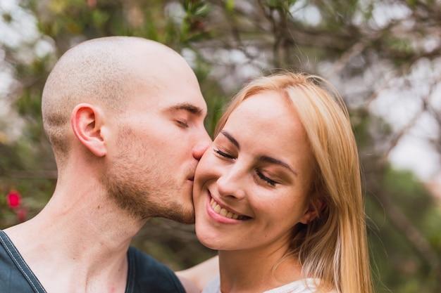 Schöne junge frau bekommt einen kuss auf die wange, während ihre augen geschlossen sind - porträt einer entzückenden jungen frau, die sich in einem park entspannt und von ihrem freund geküsst wird.