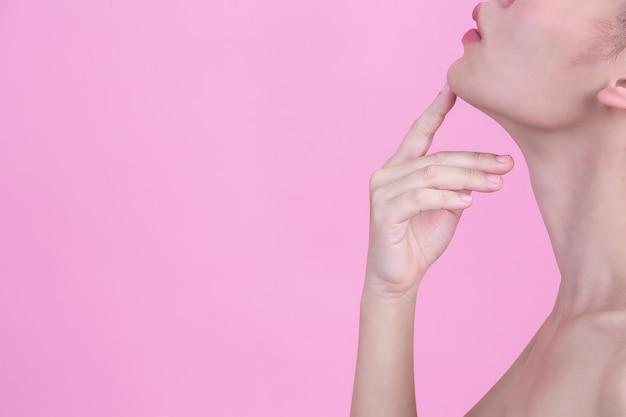 Schöne junge frau berührt ihr kinn mit ihrem zeigefinger auf rosa wand.