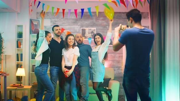 Schöne junge frau bläst küsse, umgeben von freunden, während der mann auf der party mit dem smartphone gruppenfotos macht.