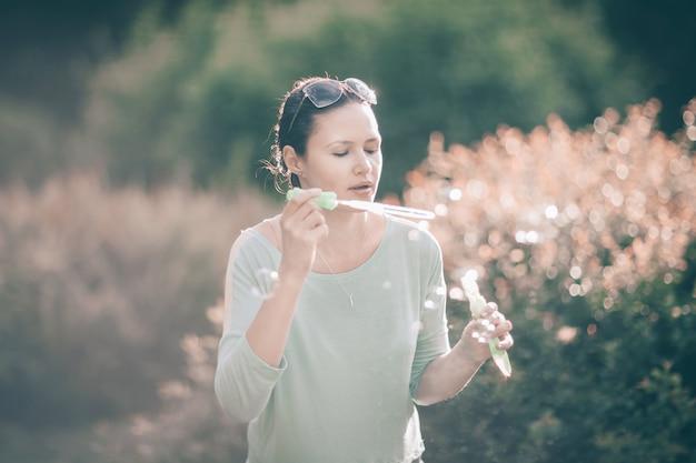 Schöne junge frau bläst seifenblasen im park sonnig