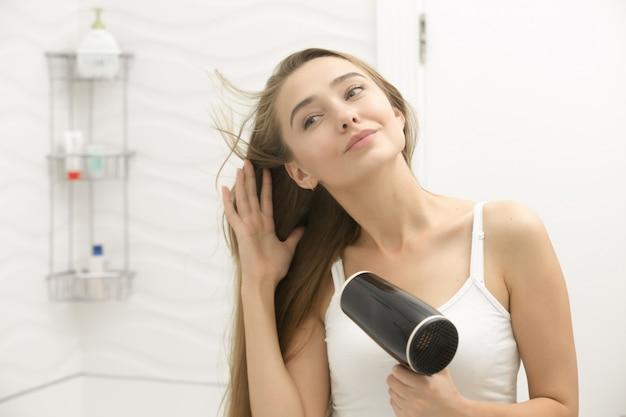 Schöne junge frau blick auf den spiegel trocknen haare