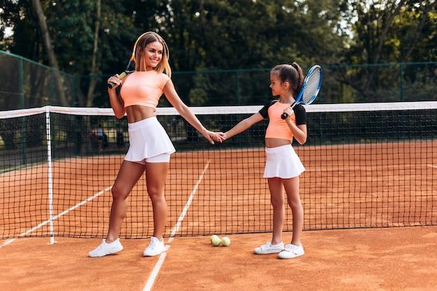 Schöne junge frau brachte ihre tochter zum tennisplatz