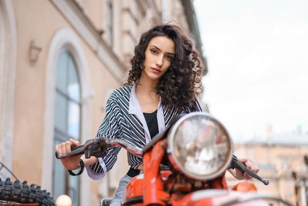 Schöne junge frau brünette mit lockigem haar sitzt auf einem roten motorrad