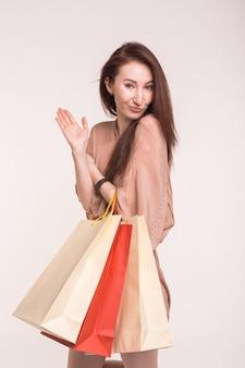 Schöne junge frau der asiatischen brünette, die in weiß mit bunten einkaufstaschen steht.