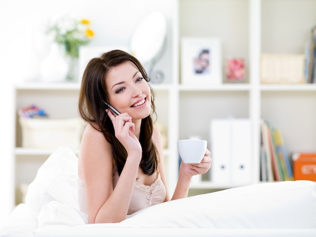 Schöne junge frau der brünetten, die durch handy spricht und einen kaffee trinkt
