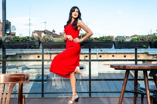 Schöne junge frau der brünetten, die rotes kleid trägt, das auf der straße modefoto geht