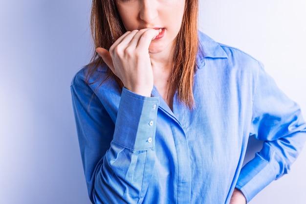 Schöne junge frau des porträts, die ihre nägel als symbol der nervosität oder hysterie beißt. nerven konzept