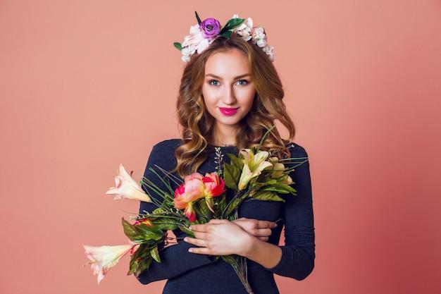 Schöne junge frau des romantischen frühlingsporträtporträts mit langen gewellten blonden haaren im kranz der frühlingsblumen, die mit blumenstrauß über rosa hintergrund aufwerfen.