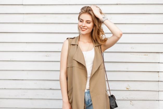 Schöne junge frau des slawischen aussehens mit einem schönen lächeln mit dem lockigen haar in den modischen sommerkleidern, die nahe einer weinleseweißholzwand an einem warmen sommertag aufwerfen. attraktives stilvolles mädchen
