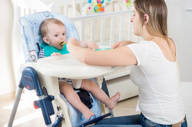 Schöne junge frau, die 9 monate altes baby füttert, das im hochstuhl sitzt