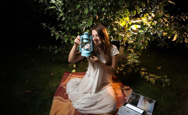 Schöne junge frau, die alte laterne beim sitzen im nachtgarten betrachtet