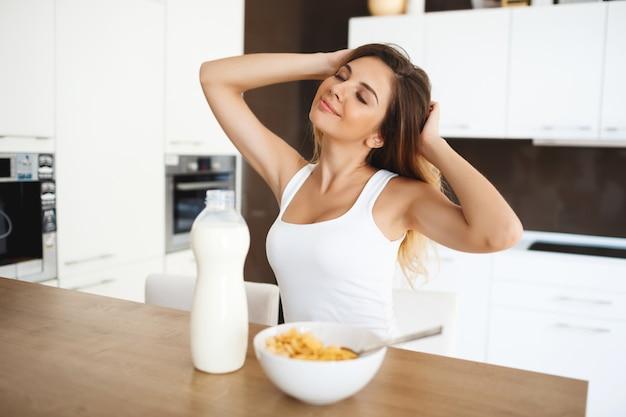Schöne junge frau, die am esstisch sitzt, der schläfrig beim frühstück streckt