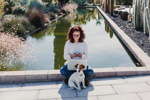 Schöne junge frau, die am laptop arbeitet. mit ihrem hund außerdem. draußen. sonnig
