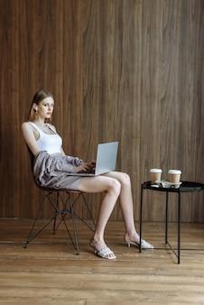 Schöne junge frau, die am laptop arbeitet, während sie internet und technologie nutzt