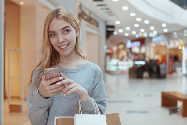 Schöne junge frau, die am lokalen mall kauft