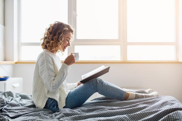 Schöne junge frau, die am morgen auf bett sitzt, buch liest, weißen strickpullover trägt, kaffee trinkt