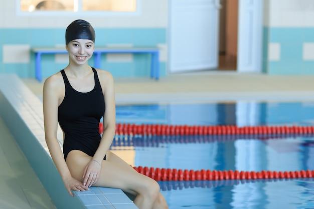 Schöne junge frau, die am pool sitzt und kamera betrachtet.