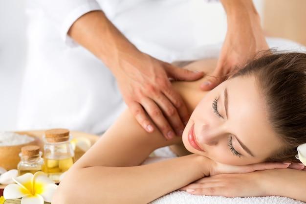 Schöne junge frau, die am spa-salon liegt. haut- und körperpflege-, entspannungs-, massage- und kosmetikkonzept