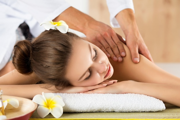 Schöne junge frau, die am spa-salon liegt. haut- und körperpflege, gesunder lebensstil, entspannung, massage und kosmetikkonzept