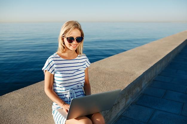 Schöne junge frau, die am strand mit laptop sitzt