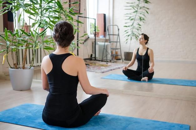 Schöne junge frau, die am studio meditiert. frau, die nachdem dem trainieren sich entspannt