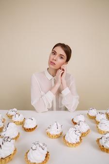 Schöne junge frau, die am tisch mit cupcakes sitzt