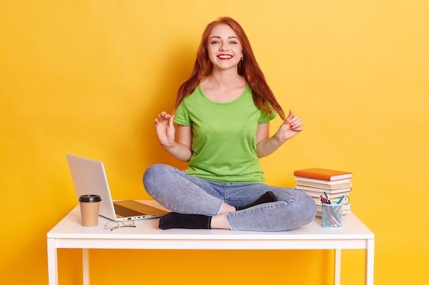 Schöne junge frau, die am tisch mit gekreuzten beinen nahe weißem laptop sitzt, gewinnende weibliche kleider lässiges t-shirt und jeans, lächelnd in die kamera schauend