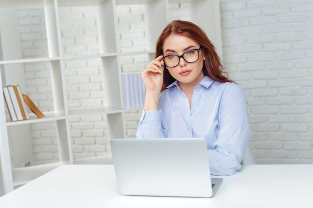 Schöne junge frau, die an computer arbeitet